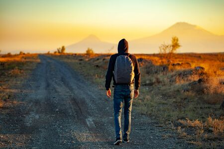 man in road at sunset Imagens