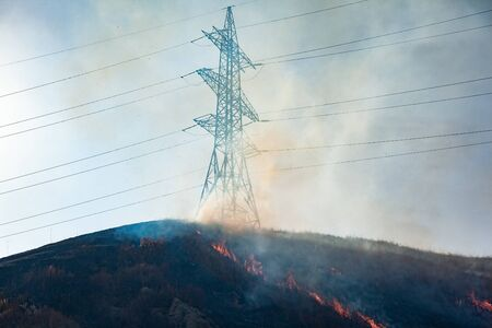 Fire in a field with electricity tower