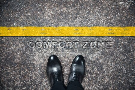 man shoes with comfort zone text on asphalt