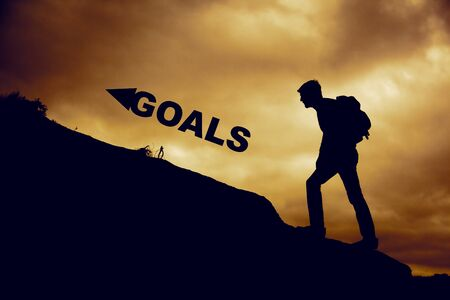 Man in mountain with goals text in sunset Imagens