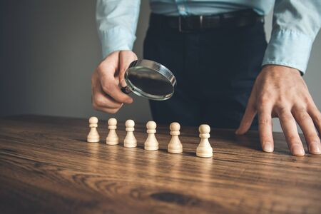 man hand magnifier with chess on table Stock Photo