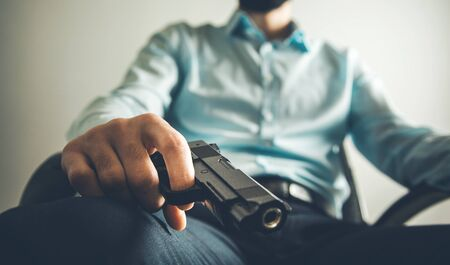 sitting man hand gun in home