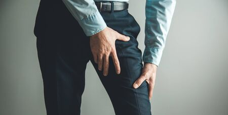 man thigh pain from cramp on gray background Stock Photo