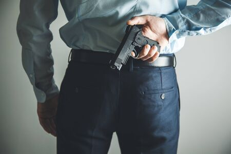 man hand gun in back Stock Photo