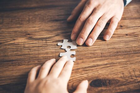 Group of Business people hands are holding jigsaw puzzle on desk