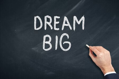 man written dream big text on chalkboard