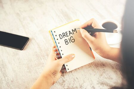 woman written dream big text on notepad