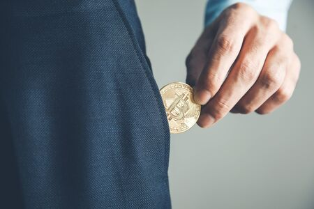 business man pocket bitcoin on gray background