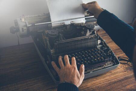 manos masculinas escribiendo una máquina de escribir en la mesa
