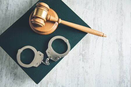 handcuffs and judge on books on table