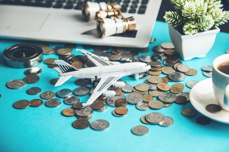 airplane with  coins on keyboard on table