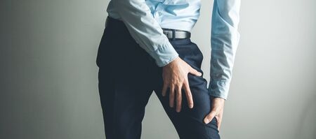 man thigh pain from cramp on gray background Stockfoto