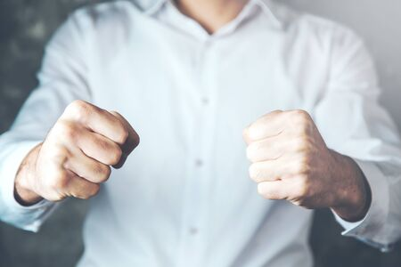young business man hand fists on the dark background