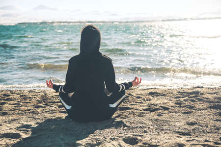 woman meditates in a lotus pose on the beach sitting