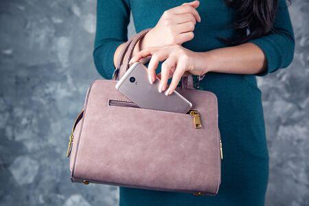 Frau Handtelefon auf Taschentasche auf grauem Hintergrund