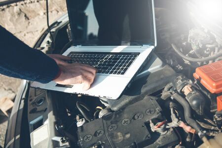 man hand computer on car in nature