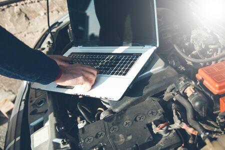 Mann Handcomputer auf Auto in der Natur
