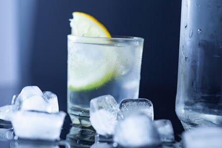 lemon on vodka with ice on table