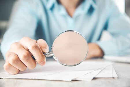 man hand magnifier and document on desk