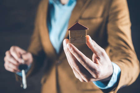 man hand house model with key on dark background Stock Photo