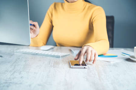 woman working in phone with computer in office