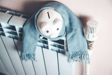 piggy bank with scarf on Heating System Stock Photo