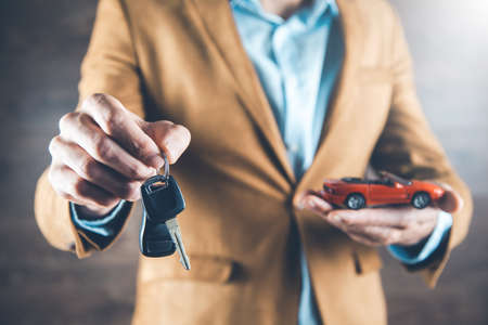 man hand car model with key on dark background