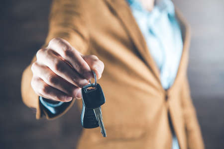 man hand car key on dark background