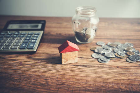 house model with coins and calculator on table