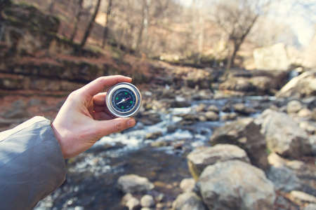 man hand compass with forest in spring
