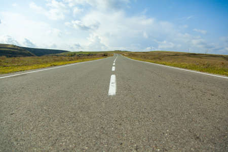 landscape with asphalt road under the blue sky