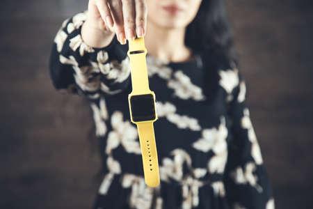 woman hand yelow smart watch on dark background 版權商用圖片