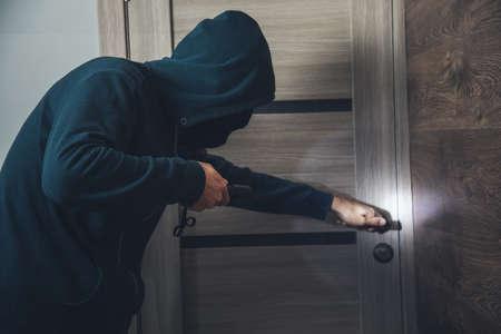 man burglar sneaking into the house with flashlight
