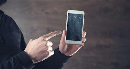 man hand broken phone on the dark background
