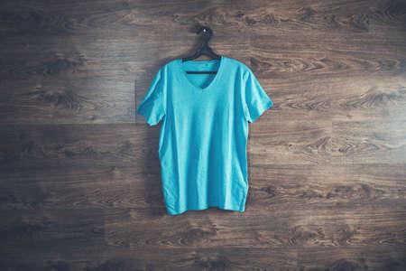 man blue t-shirt in hanger on the dark background 版權商用圖片