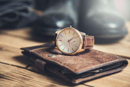 watch on wallet with shoes on table Stock Photo