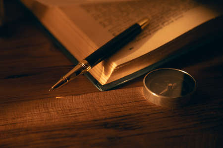 pen and book with compass on the table
