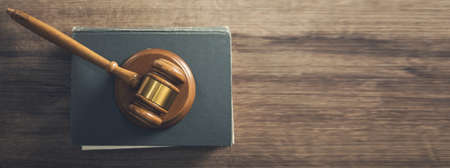Wooden judges gavel lying on a law book