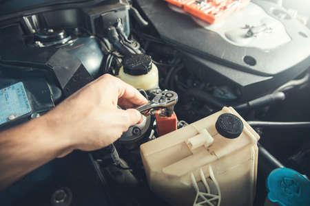 Car mechanic male worker using socket wrench