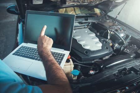 Professional car mechanic working in auto repair service using laptop on car Archivio Fotografico