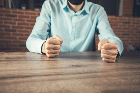 Businessman with clenched fist on the desk at office