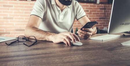 young man working from office using smart phone and computer