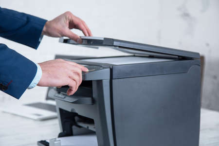 young man working copy machine in the office
