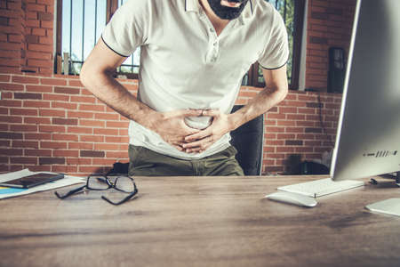 Young man suffering from stomachache in office