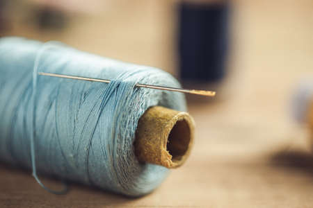 needle on the blue thread on the table