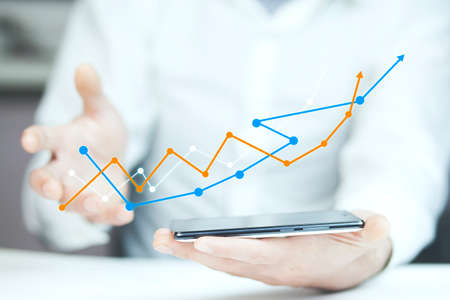 graph growth in phone screen in man hand