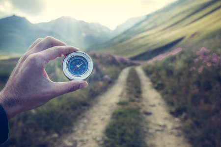 young traveler holding compass in mountain