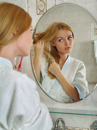 woman bathrobe: The beautiful girl with blond hair looks in a mirror in a bathroom