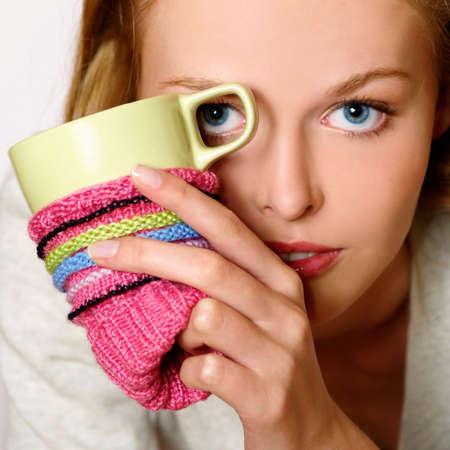 Girl drinking hot coffee or tea, having fun, close up          photo