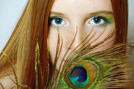 Portrait of elegant  redhead girl with feather of peacock     photo